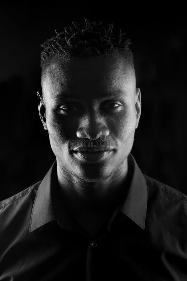Портрет африканского человека на черной предпосылке, серьезный стоковое фото