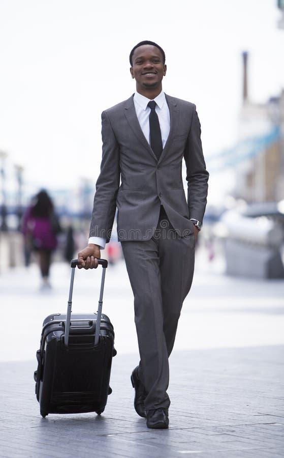 Портрет Афро-американского бизнесмена усмехаясь и вытягивая чемодан стоковое фото