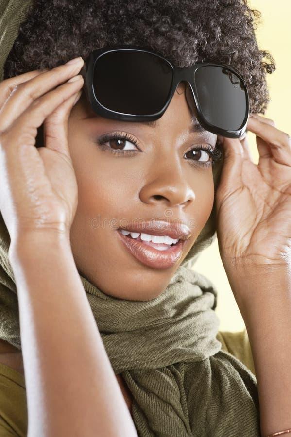 Портрет Афро-американской женщины держа солнечные очки с палантином круглый ее шея над покрашенной предпосылкой стоковые изображения
