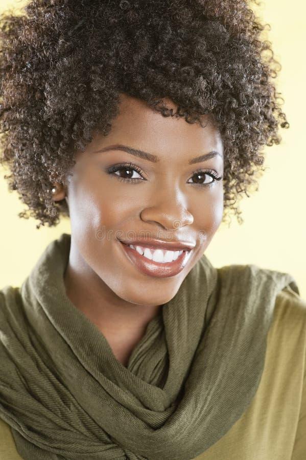 Портрет Афро-американской женщины усмехаясь с палантином круглым ее шея над покрашенной предпосылкой стоковая фотография