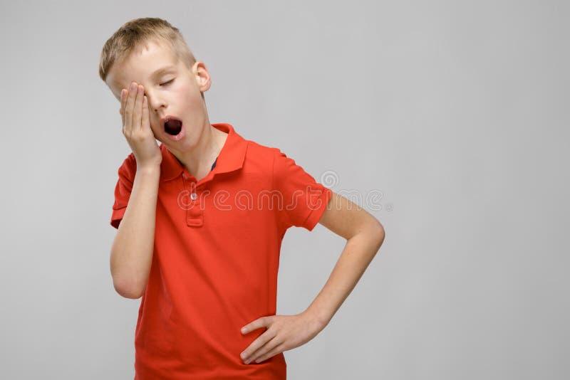 Портрет белокурого кавказского унылого мальчика в оранжевой футболке хотеть спать зевающ на серой предпосылке стоковая фотография rf