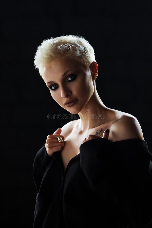 Портрет белокурой девушки с короткой стильной стрижкой на темной предпосылке стоковое фото rf