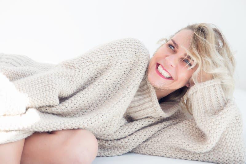 Портрет белокурой женщины в бежевом свитере лежа в кровати стоковое изображение rf