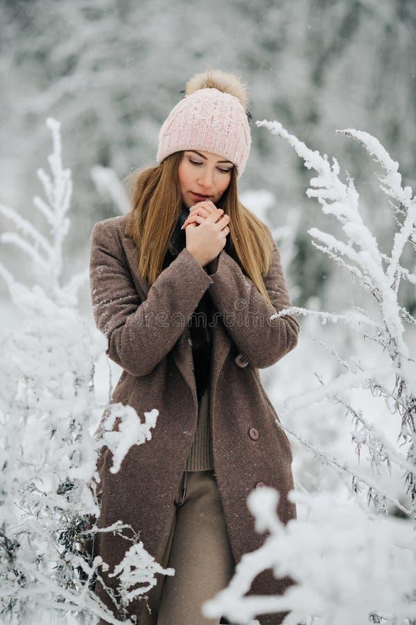 Портрет белокурой женщины в шляпе смотря камеру на прогулке в лесе зимы стоковое изображение