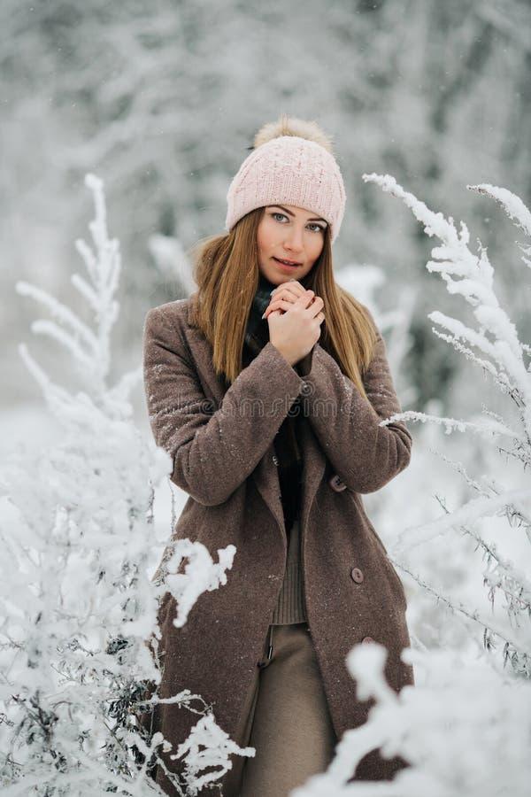 Портрет белокурой женщины в шляпе смотря камеру на прогулке в лесе зимы стоковые фото