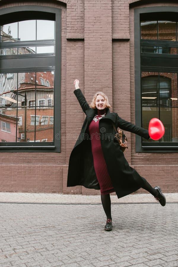 Портрет белокурой курчавой девушки представляя с воздушным шаром красного сердца форменным стоковые изображения rf