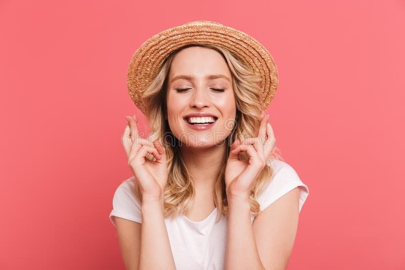 Портрет белокурой соломенной шляпы содержания женщины 20s нося держа пальцы пересеченный и желая для везения стоковое изображение rf