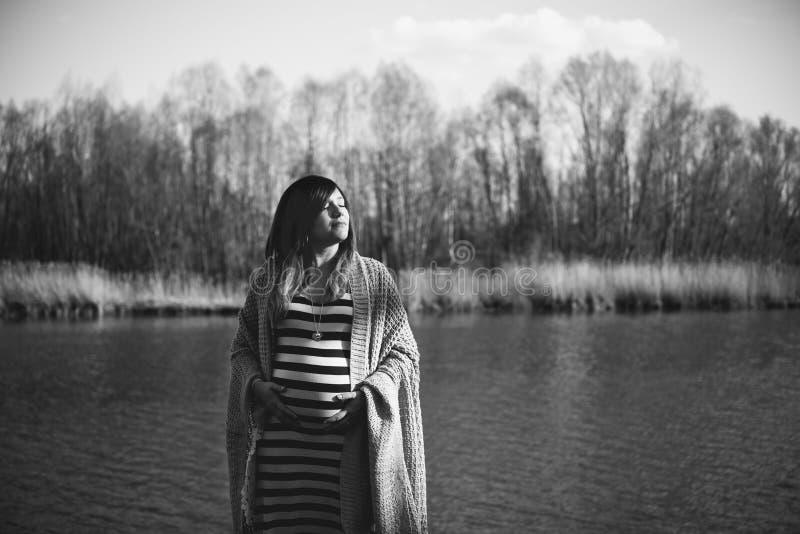 Портрет беременной женщины в береге к реке стоковое изображение