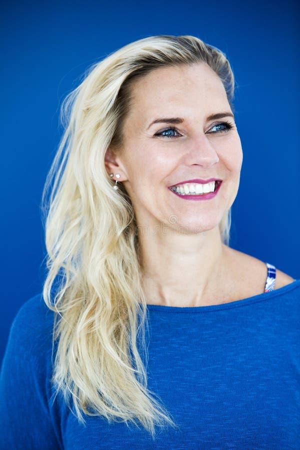 Портрет белокурой женщины в голубом свитере стоковое изображение rf