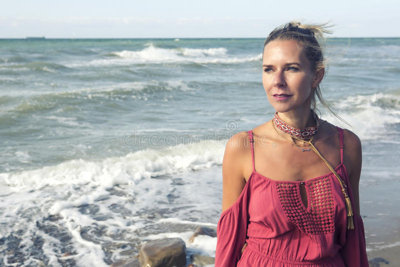 Портрет белокурой женщины в красном платье океаном стоковое фото rf