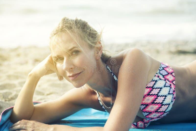 Портрет белокурой женщины лежа на пляже стоковая фотография