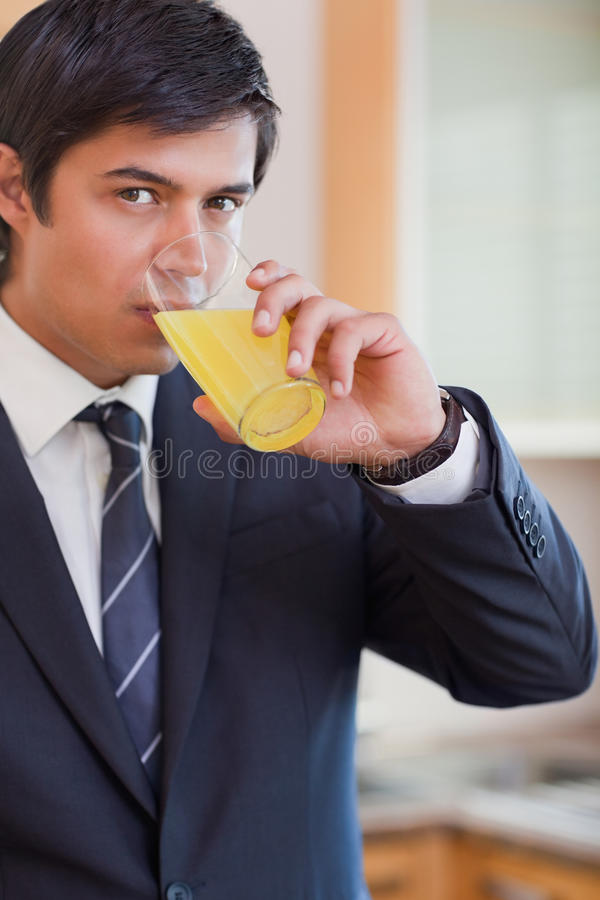 Портрет бизнесмена выпивая апельсиновый сок стоковое изображение rf