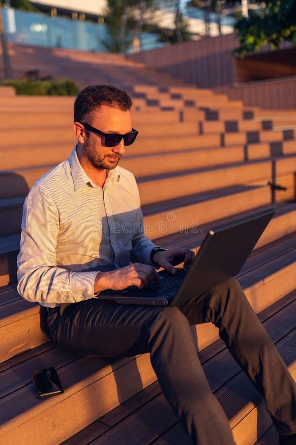 Портрет бизнесмена используя ноутбук и сидящ на лестницах outdoors на заходе солнца стоковые фото