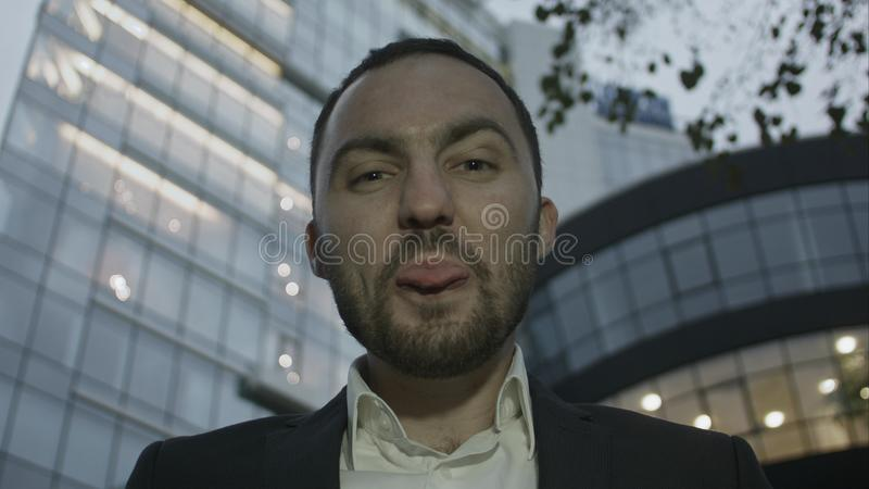 Портрет бизнесмена шутя и показывая язык против офисного здания стоковые фотографии rf