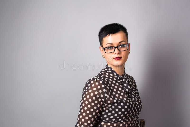 Портрет бизнес-леди или творческого профессионала с eyeglasses Серая предпосылка, с космосом экземпляра стоковое изображение rf