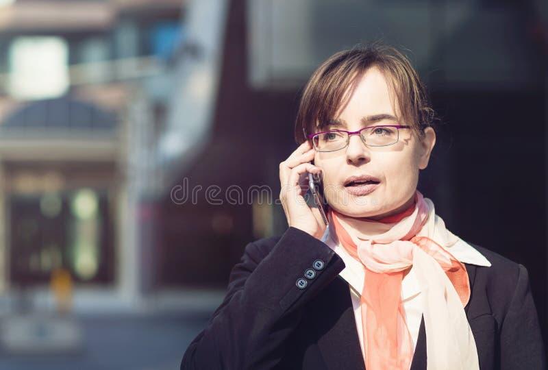 Портрет бизнес-леди в стеклах стоя в городе и говоря на телефоне стоковая фотография rf
