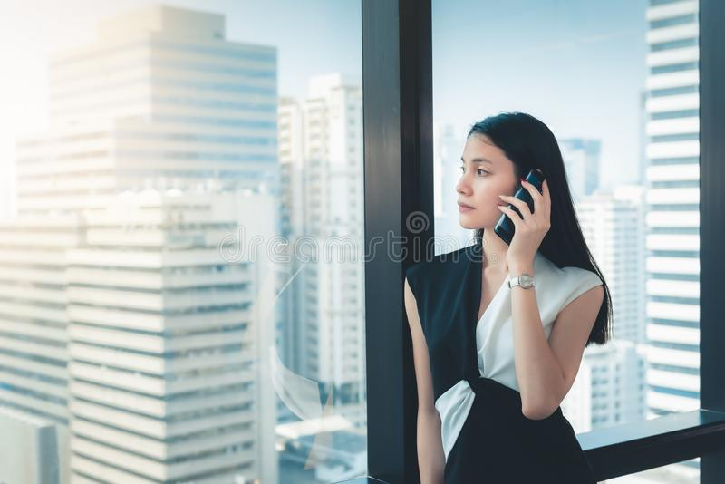 Портрет бизнес-леди говорит на мобильном телефоне в ее офисе , Красивый азиатской женщины вызывает к кто-то на ее клетке стоковая фотография rf