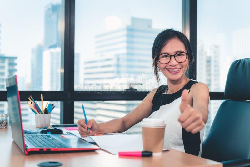 Портрет бизнес-леди Woking на ее рабочем столе таблицы в рабочем месте офиса, привлекательной красивой коммерсантке усмехаясь и стоковая фотография rf
