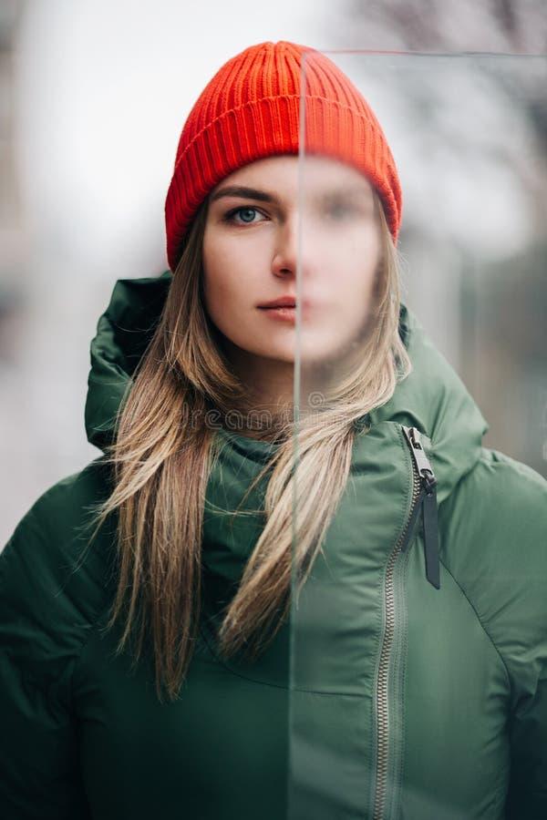 Портрет блондинкы в зеленой куртке и красной шляпе около стекла стоковая фотография