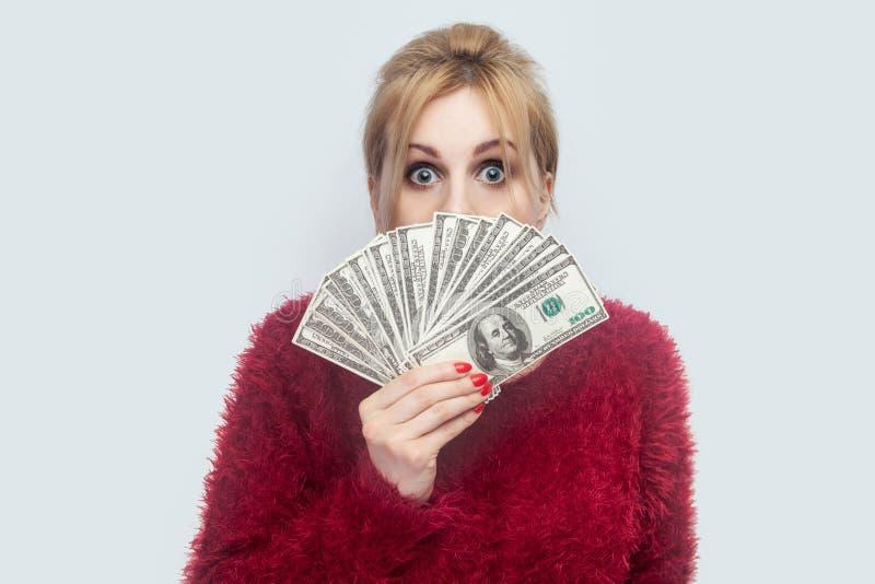 Портрет богатой привлекательной молодой взрослой коммерсантки в красном положении блузки и вентилятора показывать долларов наличн стоковые изображения rf