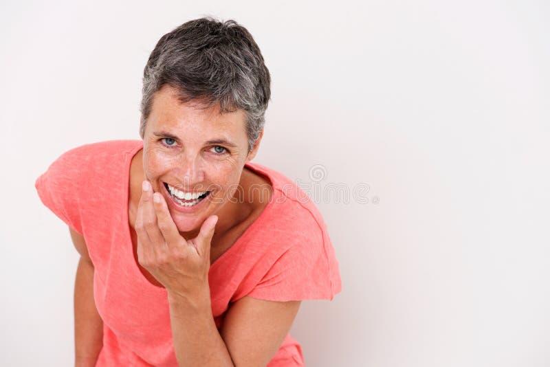 Портрет более старой женщины смеясь над против белой предпосылки стоковые фото