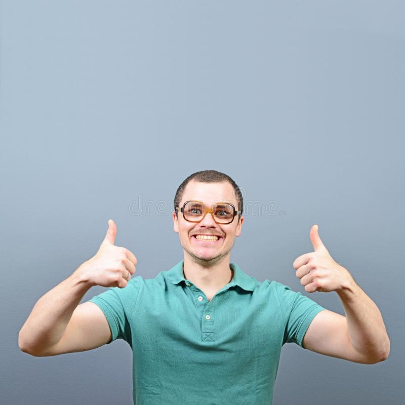 Портрет большого пальца руки показа человека вверх по знаку с пустым пространством над его головой для вашего текста против серой стоковые изображения