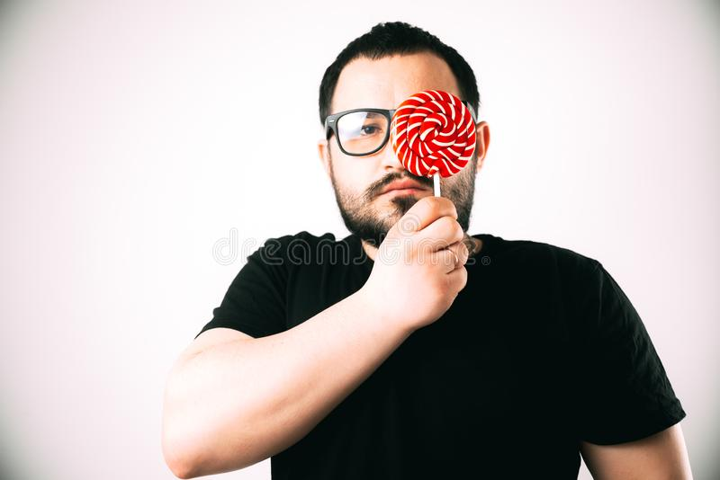Портрет бородатого человека со стеклами с круглым красным леденцом на палочке стоковое фото
