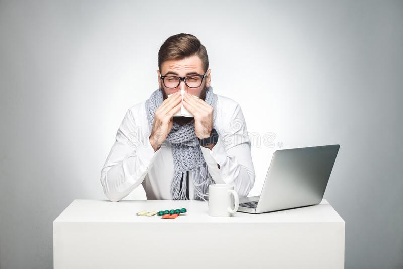 Портрет босса больного scribble молодого в белой рубашке, шарф и черный галстук сидят в офисе и потребности закончить важный отче стоковые фото