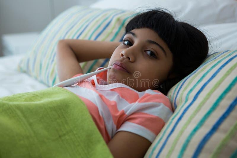 Портрет больной девушки с термометром в рте дома стоковое изображение