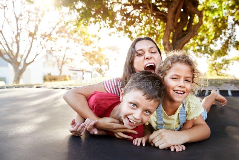 Портрет братьев с подростковой сестрой играя на на открытом воздухе батуте в саде стоковое фото rf