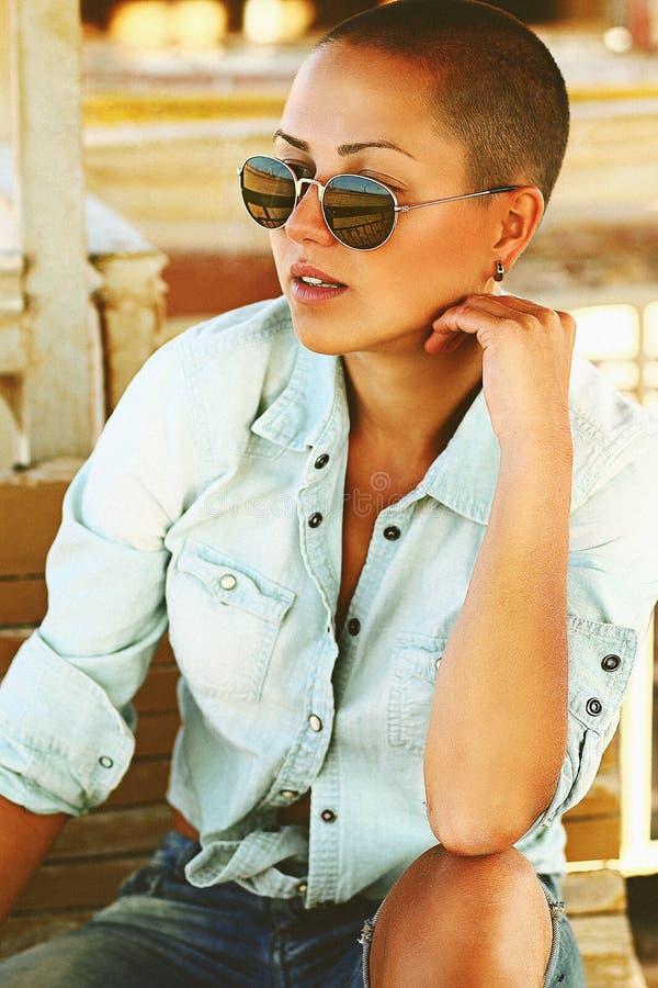 портрет Брить-головой девушки лицевой, сторона suntan, черные стильные солнечные очки, футболка одежд джинсов моды и шорты, корич стоковые изображения rf