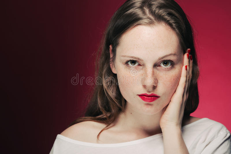 Портрет веснушки женщины на предпосылке цвета красной и розовой стоковое изображение rf