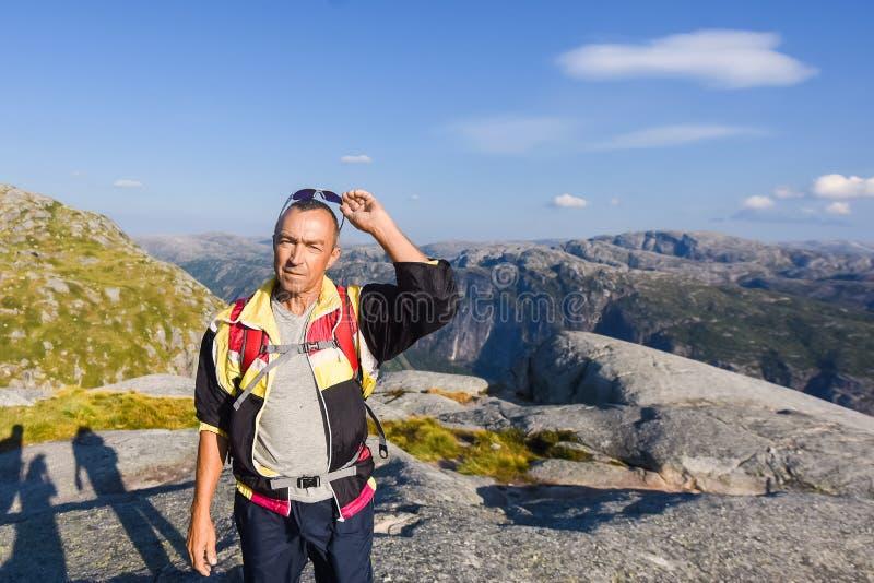 Портрет весьма перемещения плана для красивого старика на камне kjerag в горах Норвегии, s стоковые фото