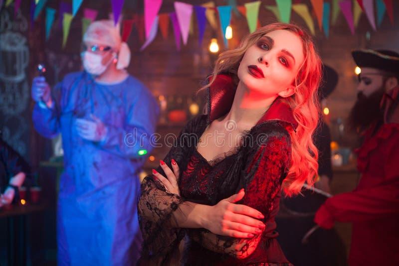 Портрет взгляда со стороны красивой молодой женщины одеванный как ведьма с серьезной стороной на сходе хеллоуина стоковое фото rf