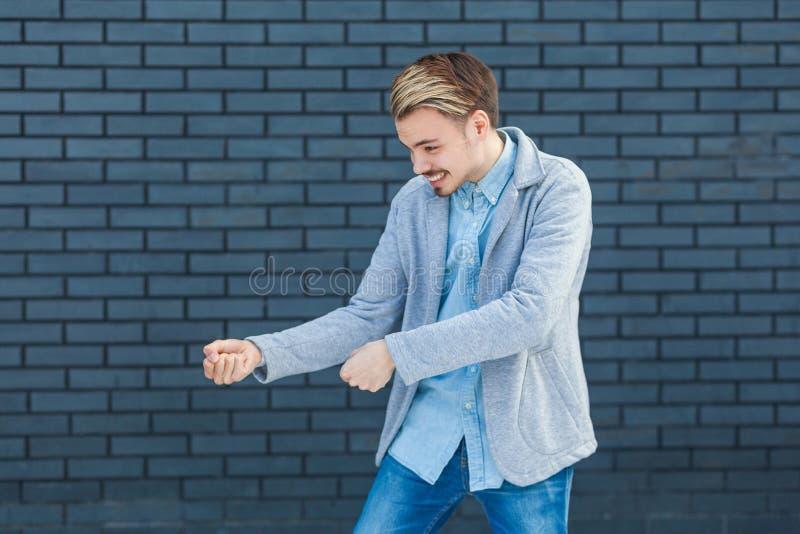 Портрет взгляда со стороны профиля внимательного красивого молодого белокурого человека в положении непринужденного стиля в вытяг стоковое изображение rf