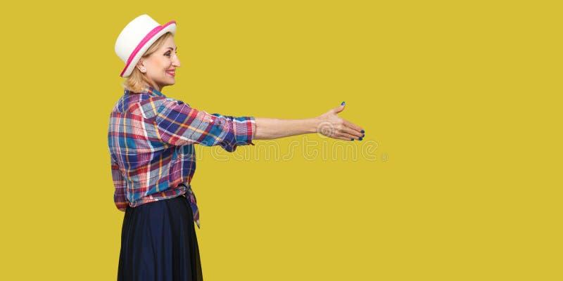 Портрет взгляда со стороны профиля счастливой современной стильной зрелой женщины в непринужденном стиле с положением шляпы, смот стоковая фотография rf