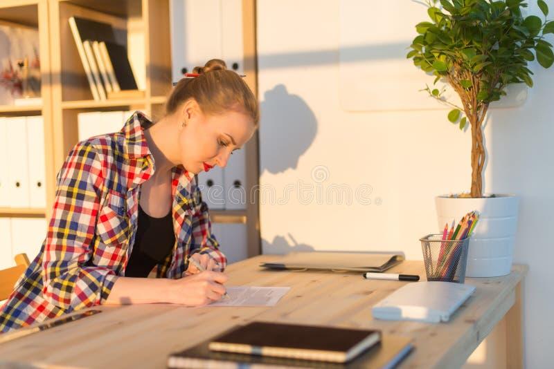 Портрет взгляда со стороны дизайнера по интерьеру писать новый проект, сидя на рабочем месте Молодое умное чтение студентки стоковое фото rf