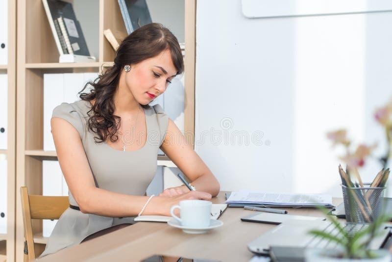 Портрет взгляда со стороны усаживания коммерсантки сконцентрировал, пишущ, организующ ее расписание в светлом офисе стоковое фото