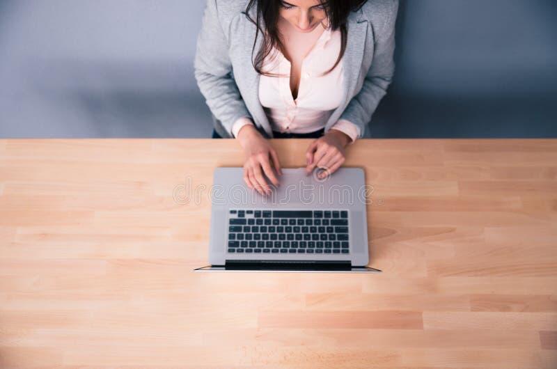 Портрет взгляд сверху женщины используя компьтер-книжку стоковое изображение