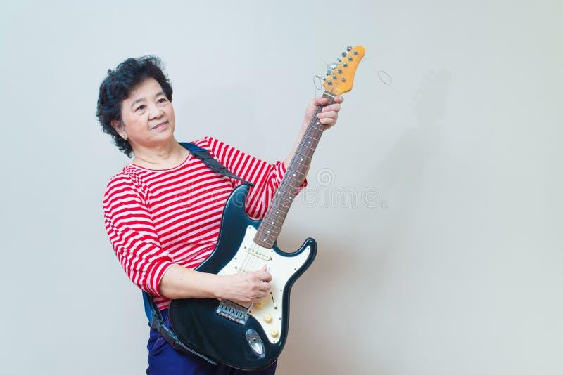 Портрет взрослой азиатской женщины с тонной специальности электрической гитары стоковое изображение