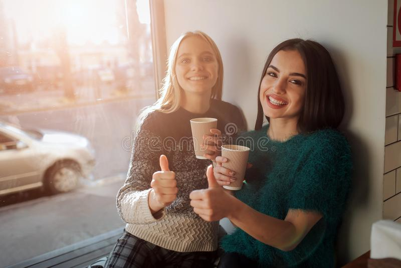 Портрет вид спереди 2 смешных друзей с большими пальцами руки поднимает и смотрящ к камере стоковые фотографии rf