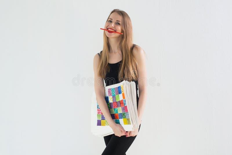 Портрет вид спереди молодого женского художника держа изображения нарисованные рукой пакует, усмехающся с карандашем в ее зубах стоковая фотография rf