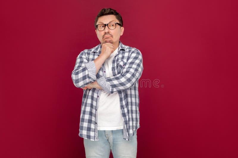 Портрет внимательной красивой середины постарел бизнесмен в случайном checkered положении рубашки и eyeglasses, смотря прочь и стоковое изображение rf