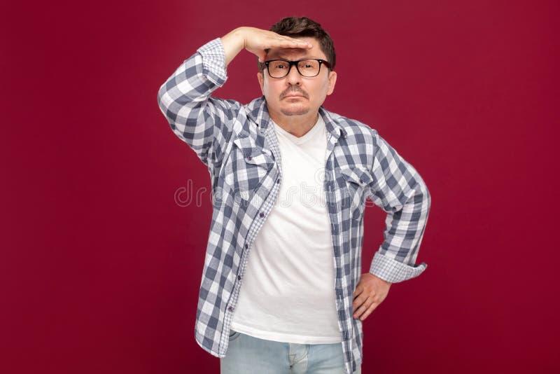 Портрет внимательной красивой середины постарел человек в случайной checkered рубашке и eyeglasses стоя с рукой на лбе и смотреть стоковое изображение rf