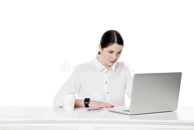 Портрет внимательной серьезной привлекательной коммерсантки брюнета в белой рубашке сидя с ноутбуком и смотря дисплей и стоковая фотография rf