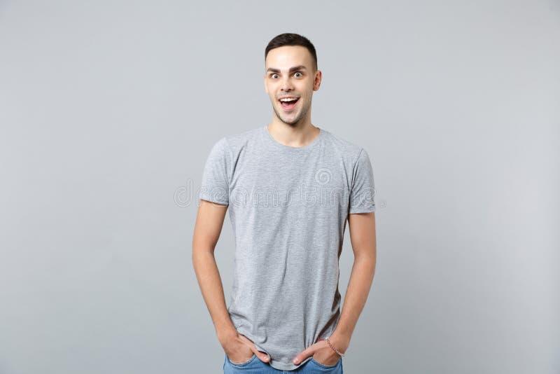 Портрет возбужденного молодого человека в случайных одеждах держа рот открытый, держа руки в карманах изолированных на серой стен стоковые изображения rf