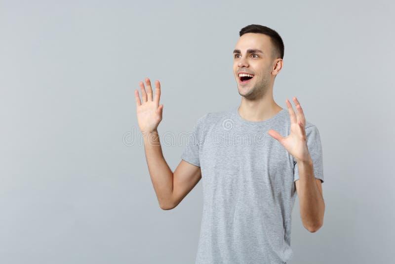 Портрет возбужденного молодого человека в случайных одеждах смотря в сторону, поднимая распространяя руки, держа рот раскрывает и стоковое изображение rf