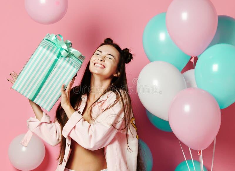 Портрет возбужденной милой девушки в jaket держа присутствующую коробку изолированный над розовой предпосылкой стоковое изображение rf
