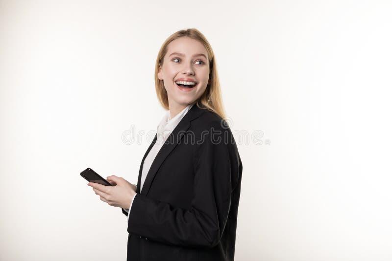 Портрет впечатленный изумил привлекательную белокурую женщину в черном костюме, держа смартфон и показывая жестами от стоковая фотография