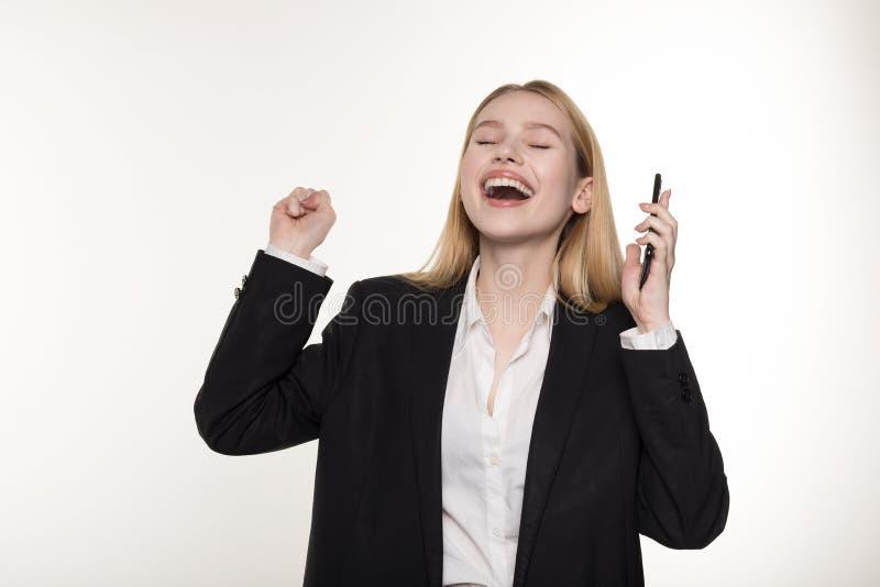 Портрет впечатленный изумил привлекательную белокурую женщину в черном костюме, держа смартфон и показывая жестами от стоковые фото